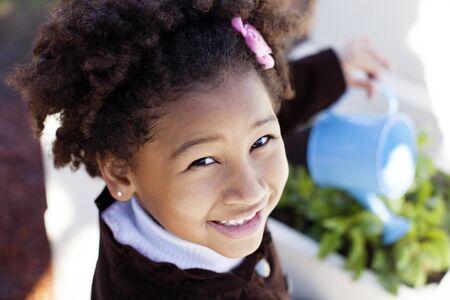 regando plantas: Happy african american little girl watering plants