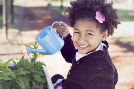 regar las plantas: Happy african american little girl watering plants