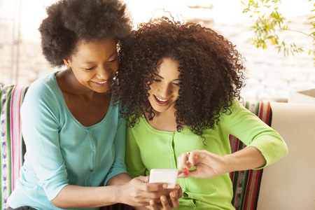 cel: African american female friends having fun with mobile phone Stock Photo