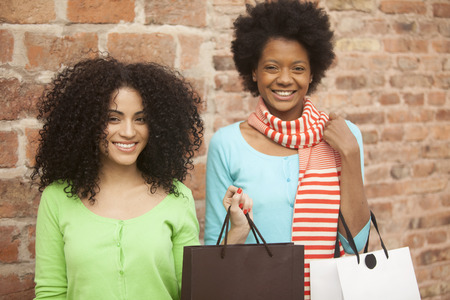 brazilian ethnicity: African american female friends with shopping bags outdoors