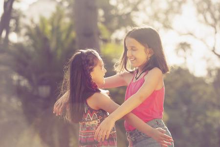 siblings: Female siblings hugging outdoors