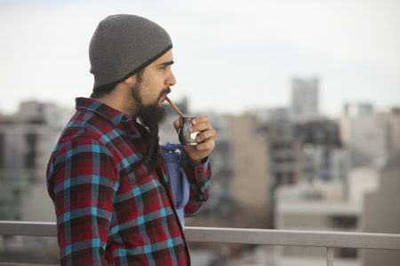 Argentinian man drinking mate ourdoors in Buenos Aires city, Argentina Stock Photo - 85868371