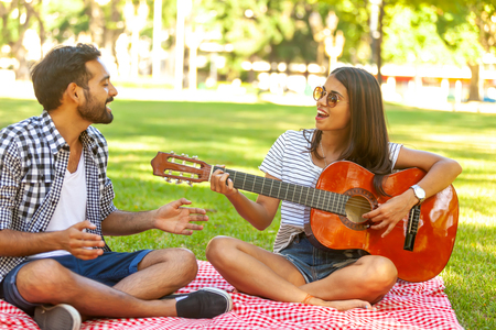 Happy couple playing guitar outdoors 版權商用圖片