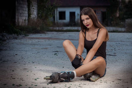 Girl with skates sitting on the concrete covered with shards of glass