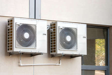 electric fixture: Air conditioning system assembled on side of a building.