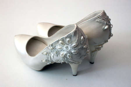 objec: White highheeled shoes with pearls on white background