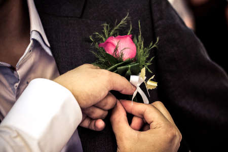 pinning: Pinning the Groom with boutonniere flowers before wedding ceremony