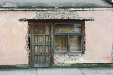 External wall of an old house painted in pink, with brown window and door. photo