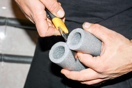 El trabajador corta la espuma aislante para tuberías Foto de archivo - 40200716