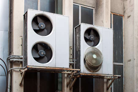 coolant: Damaged air conditioning system assembled on side of a building. Stock Photo