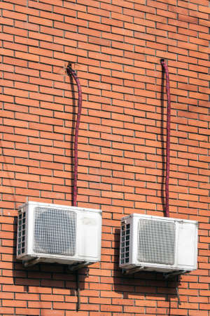 coolant: Old air conditioning outdoor units assembled on side of a building. Stock Photo