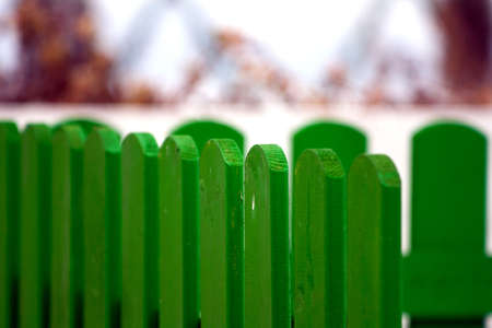 man made structure: Part of an  green hardwood fence