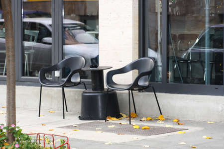 arranging chairs: empty restaurant terrace on city street