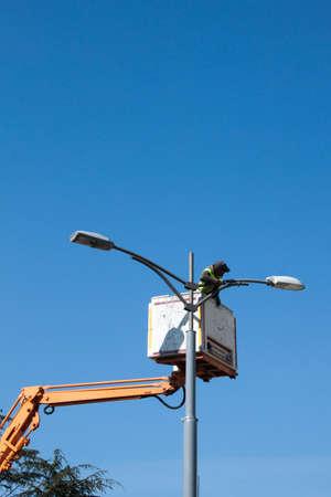 Un trabajador de la fijación de un poste de luz Foto de archivo - 40200929