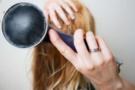 Mujer rubia joven que seca el pelo largo con el ventilador eléctrico. Fan en foco Foto de archivo - 40200934
