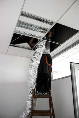 worker raises isolated flexible hose for ventilation