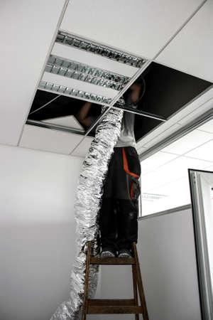 raises: worker raises isolated flexible hose for ventilation
