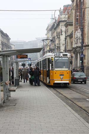 relies: Budapest, Hungary - January 3, 2014: No 47 tram passing by Budapest. A yellow tram stops at a station in Budapest, Hungary. As in many European cities, Budapest relies on an extensive tram network to move people around the metropolis. Editorial