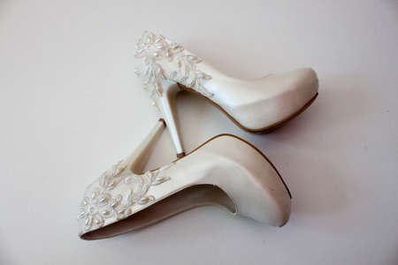 fetish wear: White shoes with pearls and high heels on a white background Stock Photo
