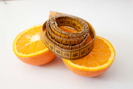 dietology: Measuring tape to oranges halves on a white background