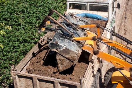 camion volquete: Excavadora vacia la suciedad en Dump Truck Foto de archivo