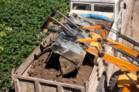 dirt: Excavator Dumping Dirt into Dump Truck Stock Photo