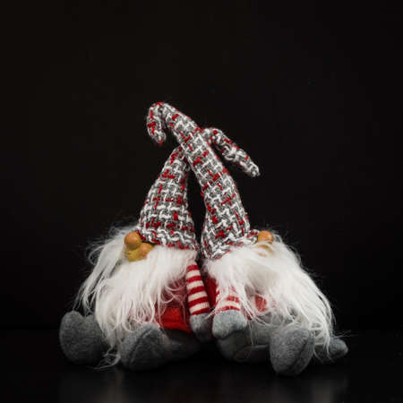 Pair of Christmas gnomes, small decorative puppets made of cloth and wood on a black background