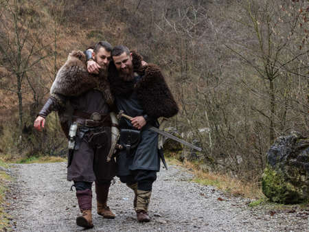 two Viking warriors walk hugged in the forest Stock Photo