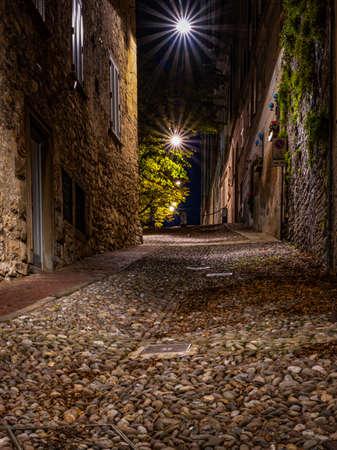 Mittelalterliche Straße, die nachts schmal in Richtung Bergamo Alta führt. Vertikales Bild des nächtlichen Stadtbildes.