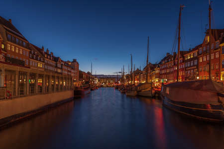 Early evening lights on the Nyhavn canal in Copenhagen, boats and night reflections