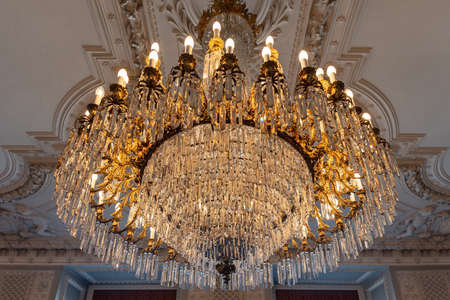 Reproduction of antique chandelier with crystals, photo set with ancient objects