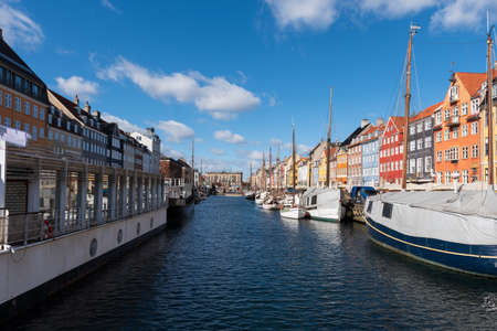 Nyhavn Canal under a blue sky with some clouds, ancient port in the center of the city of Copenhagen
