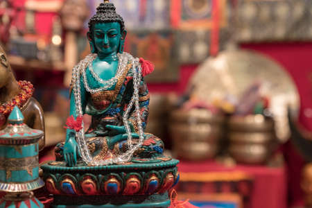 Buddha statuette with votive necklace exposed in an Asian market, horizontal image with shaded background Imagens