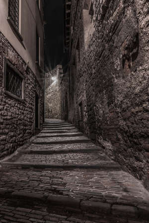 Medieval street that goes up narrow towards Bergamo Alta in the night. Vertical image of nocturnal cityscape. Stock Photo