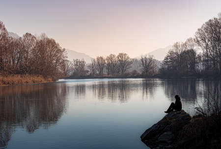 Silhouette of a person sitting on the edge of the river at sunset, Italian landscape