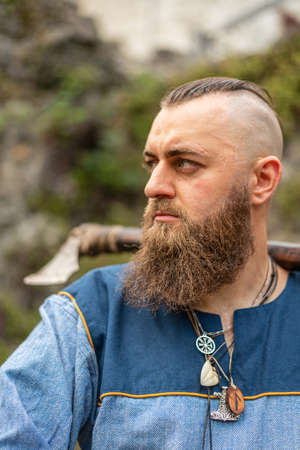 Portrait of a Viking warrior with a long beard with ax and amulets around his neck