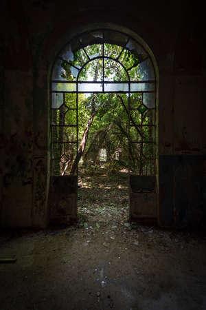 Arched door with broken windows in an old dilapidated Italian building of the twentieth century, urbex image