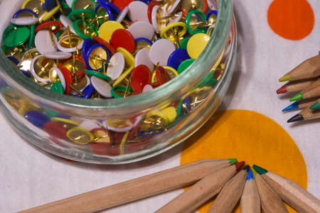colored thumbtacks in a glass jar and colored pencils horizontal image