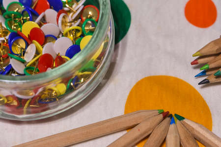 colored thumbtacks in a glass jar and colored pencils