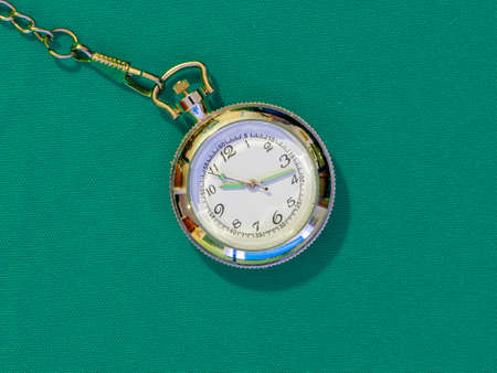 Small steel pocket watch with white dial, metal object on a uniform colored background