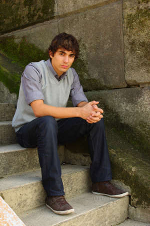 Young adult man sitting on stone stairs photo