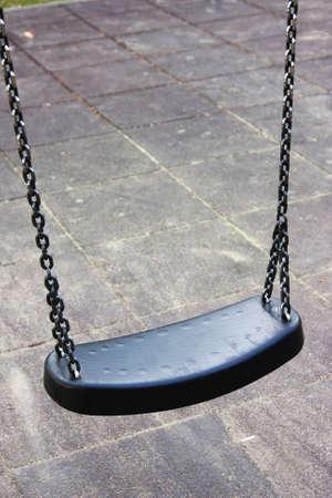 sturdy: Empty dark sturdy swing on a playground, isolated