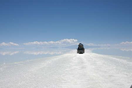 crossing the salt flats of salar de uyuni in Bolivia by suv