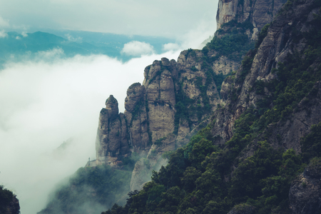 Mountains near Montserrat Abbey in Spain. Clouds and fog. Trees on cliffs. Summer holidays in mountains.