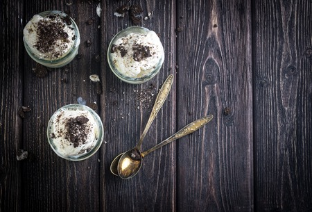 Ice cream with chocolate cookies in glass jars. Rustic wooden desk.