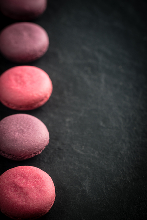 Group of macarons made of strawberries, cream, chocolate and blueberries. Rustic photo. Toned. Stock Photo