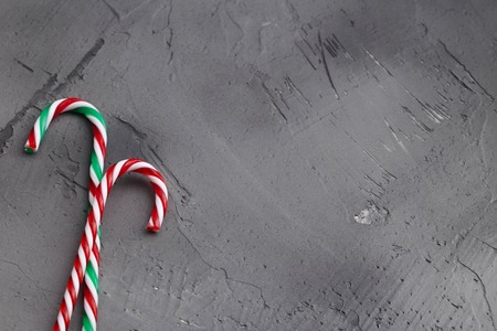 Hard candy canes on grey concrete desk. Christmas decoration. Space for text.