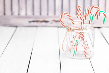 Many candy cane sticks in glass jar. Light photo. Christmas decorations. Space for text.