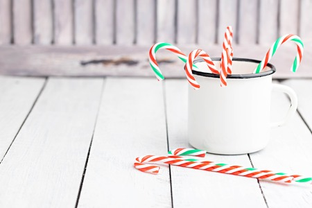 Christmas candy cane sticks in white tin cup. Light coloured photo. Space for text. 版權商用圖片