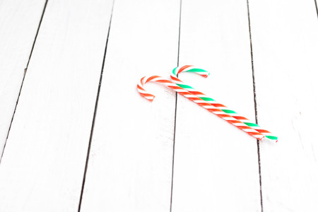 Two candy cane sticks on white wooden table. Christmas decorations. Space for text. 版權商用圖片